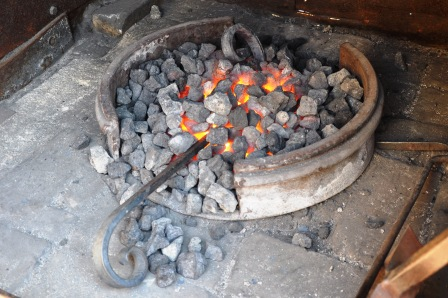 Photo of a steel scroll being heated in a coke fuelled forge for inclusion in a wrought iron gate in Adelaide