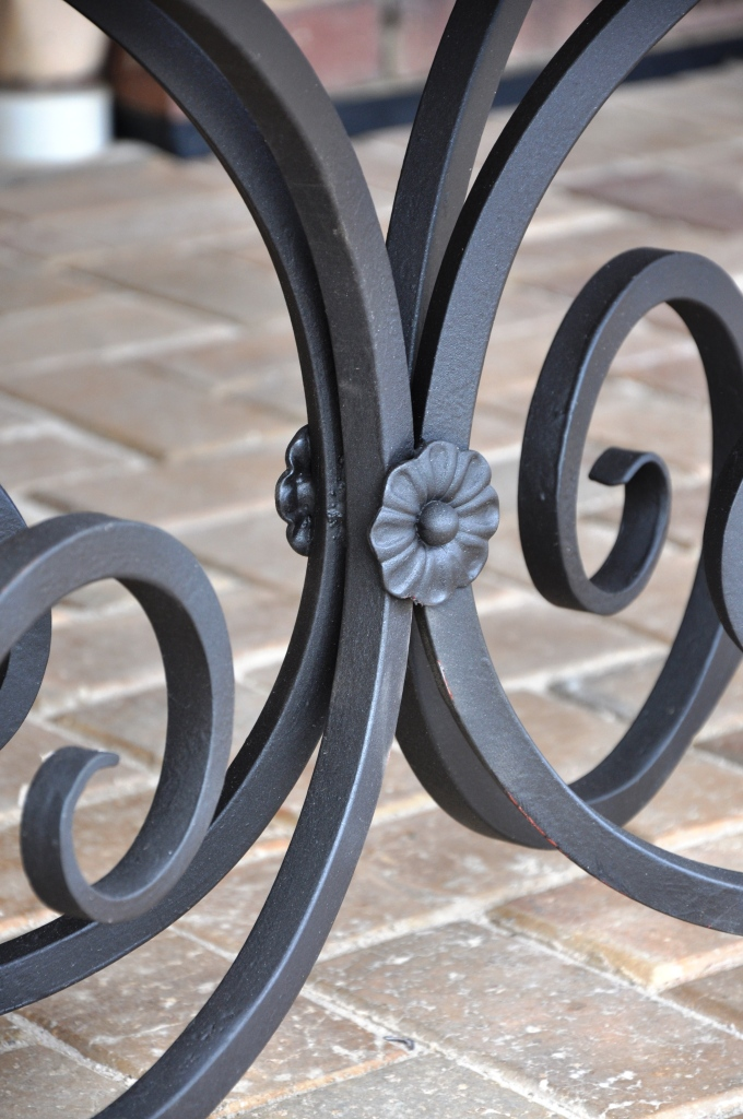 close up of wrought iron table base showing flower detail