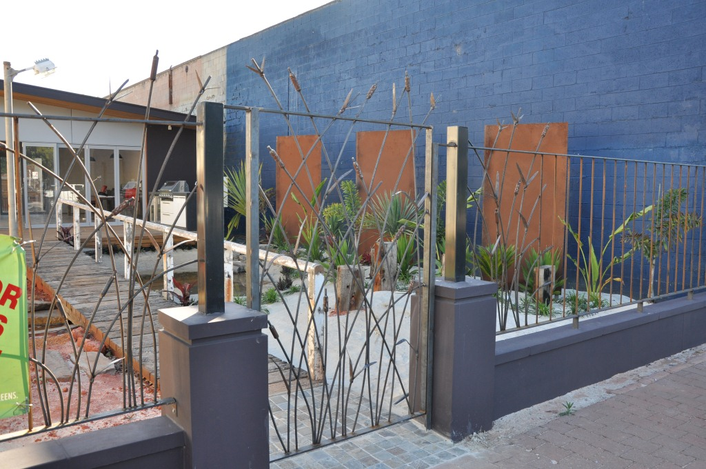 The organic forms of a wrought iron bull rush fence and steel gate add a contemporary touch to this garden design centre in Adelaide.