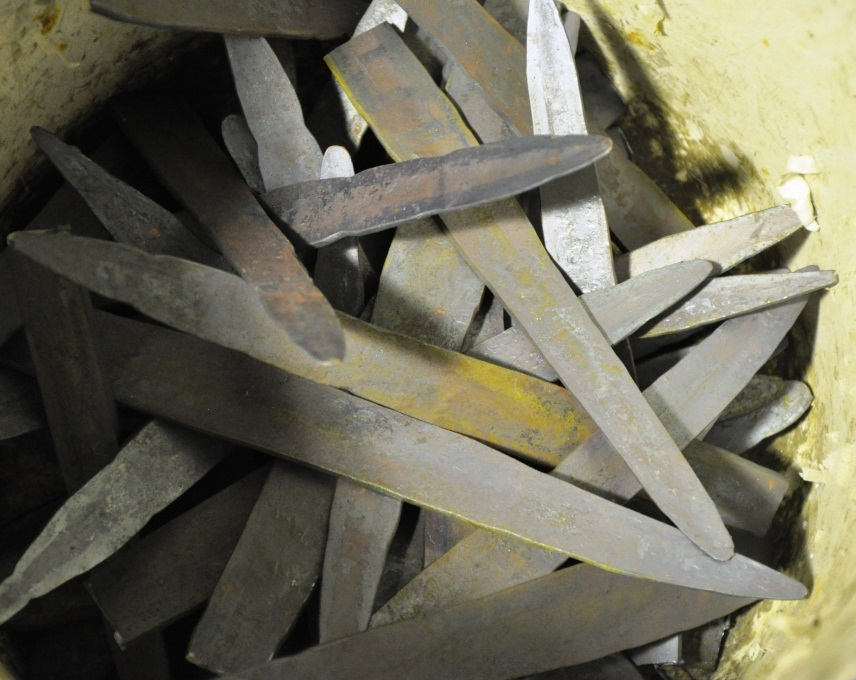 Hand forged bullrush leaves are hammered out in by Adelaide blacksmith Andrew Hood, and sit in a bucket before being individually sculpted to shape on the anvil.