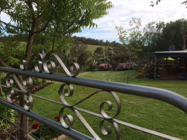Top of wrought iron and mesh gate frames the lawns of the Bridgetown Open Garden, Western Australia