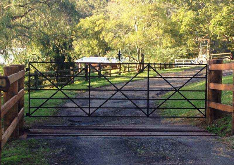 Eleanor steel driveway farm gate made by Farmweld is hinged to large heavy posts. Post and rail fences look great with Farmweld's heritage country style gates
